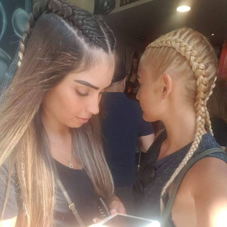 שתי בנות עומדות אחת ליד השני שתיהן עם צמות צמודות
