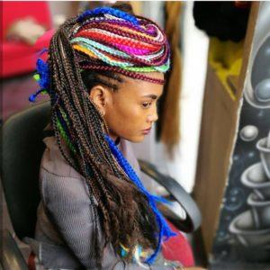 בחורה יושבת על כיסא מביט הצידה ועל הראש צמות פזורות צבעוניות