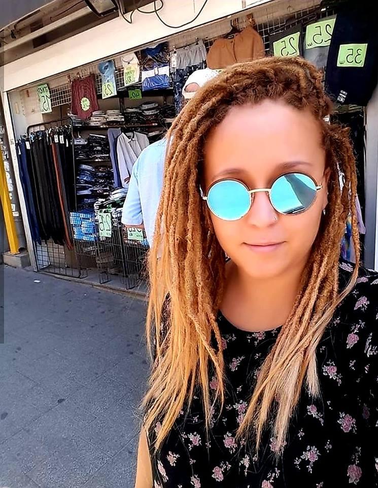 בחורה עם משקפי שמש מביטה למצלמה, כל הראש ראסטות טבעיות