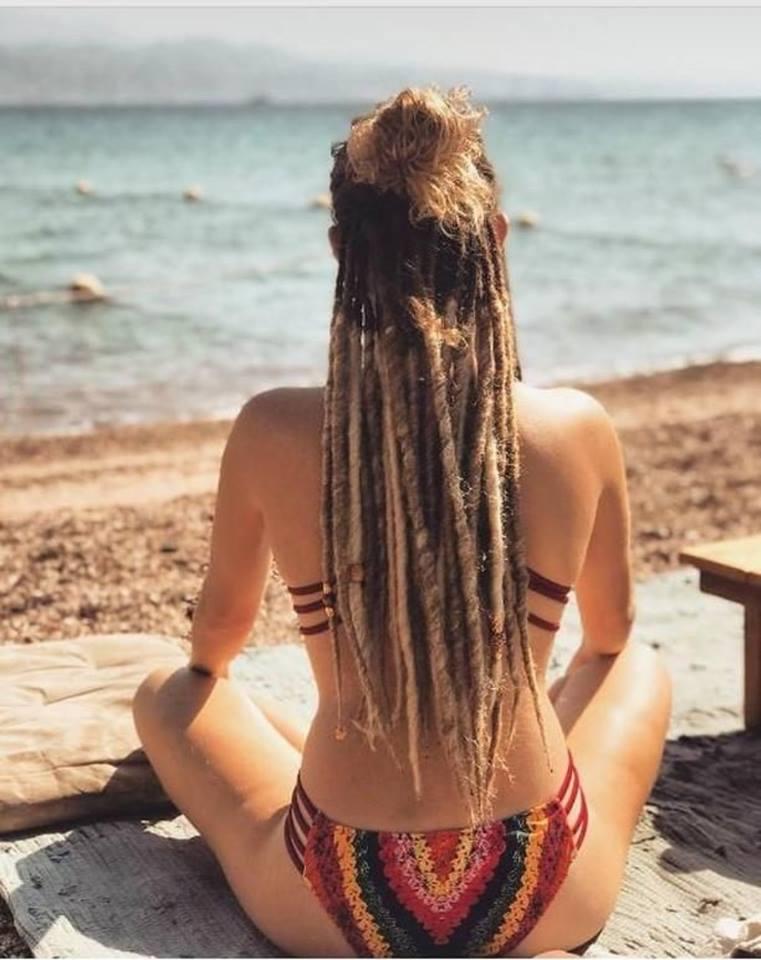 בחורה עם הגב למצלמה מביטה אל הים, השיער שלה מאחור הוא ראסטות