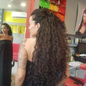 בחורה מביטה על המראה, על הראש תוספות שיער ברזילאי