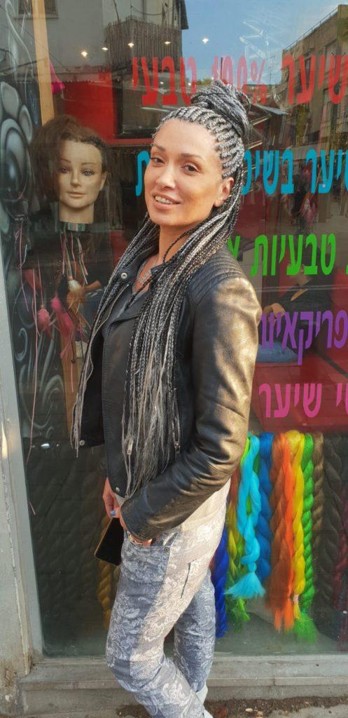 בחורה עם גקט עור מביטה על המצלמה, על הראש צמות פזורות בצבע כסוף
