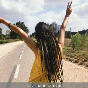 תמונה מאחור, בחורה עם חולצה צהובה וראסטות על הראש