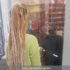 תמונה מאחור של בחורה עם סריג ירוק וראסטות בלונדיניות ארוכות