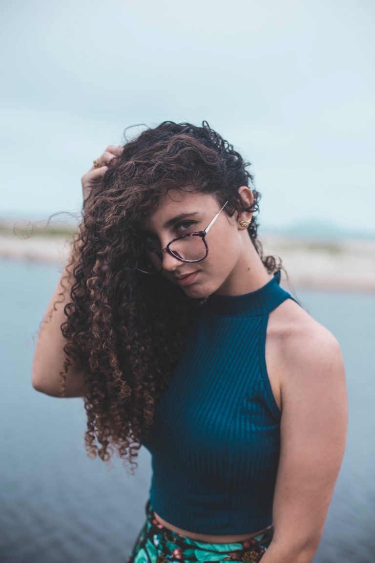 תמונה של בחורה עם משקפים ושיער חום מלא תלתלים