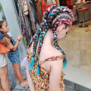 תמונה מאחור של בחורה עם 4 צמות צמודת צבעוניות