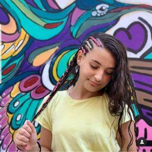 ילדה עם חולצה צהובה מסיטה את הראש הצידה ומראה את השלושה צמות בצד עם גוונים