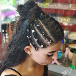 בחורה מביטה הצידה עם שלושה צמות בצד עם עגילים