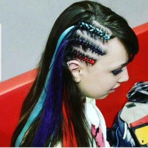 בחורה מביטה הצידה עם שלוש צמות בצד עם גוונים כחול, תכלת ואדום
