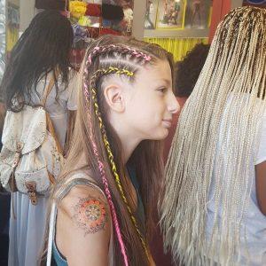 בחורה מביטה הצידה ומראה שתי צמות צבעוניות ארוכות בצד