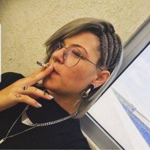 בחורה מביטה הצידה מעשנת סיגריה ומראה צמות בצד
