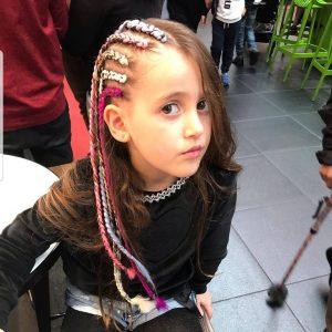 ילדה מביטה אל המצלמה ומראה חמש צמות בצד עם גוונים צבעוניים