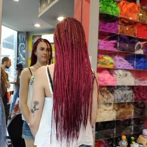 תמונה מאחורה של בחורה עם צמות פזורות בגוון אדום