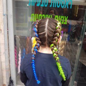תמונה מאחורה של ילדה עם צמות צמודות בצבע ירוק וכחול
