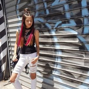 בחורה עם גינס לבן וחולצה שחורה עם צמות צמודות