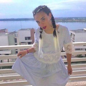 בחורה בשמלה לבנה עם צמות צמודת