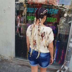 תמונה מאחור, בחורה עם מכנס גינס וחולצה לבנה פרחונית עם צמות צמודות ארוכות בצבע בלונד על הראש