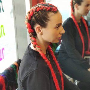 תמונה מהצד של בחורה עם צמות צמודות בצבע אדום