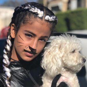 סלפי של ילדה עם צמות צמודות מחזיקה כלב
