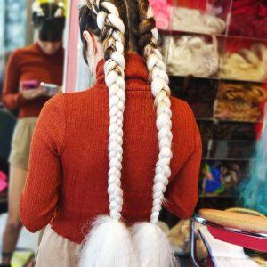 תמונה מאחור של בחורה עם צמות צמודות ארוכות בצבע לבן