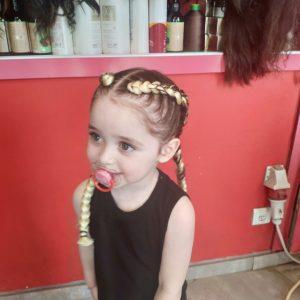 ילדה עם צמות צמודות בצבע בלונד