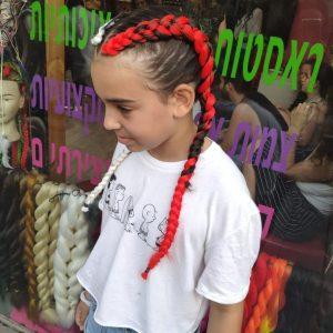 תמונה מהצד של ילדה עם צמות צמודות בצבעים של אדום ולבן