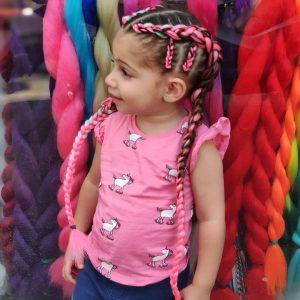ילדה עם צמות צמודות בצבע ורוד