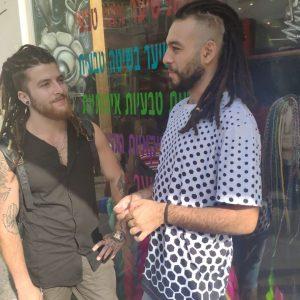 שני בחורים עם ראסטות מוהק עומדים ברחוב ומסתכלים אחד על השני