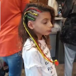 ילדה מביטה הצידה עם שלוש צמות צבעוניות בצד