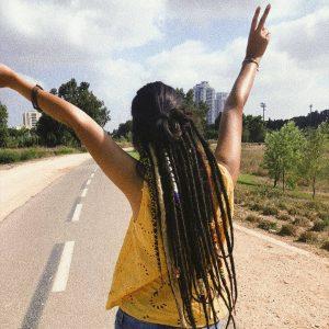 תמונה של בחורה מאחורה עם חולצה צהובה וראסטות מאחורה, מרימה את הידים לוי