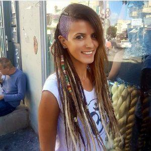 תמונה של בחורה מחוץ לקונדלראסטה עם ראסטות בגווני חום ובלונד וגלח בצד
