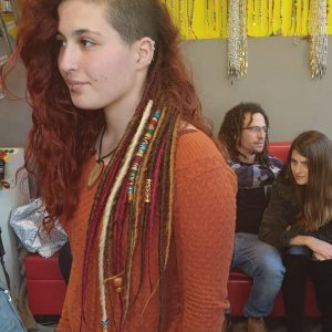 תמונה של בחורה מהצד עם ראסטות צבעוניות מאחורה וגלח בצד