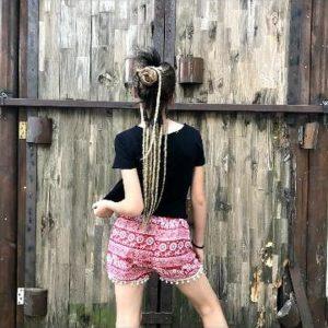 תמונה של בחורה מאחורה עם מכנס ורוד וחולצה שחורה וראסטות בקטנה