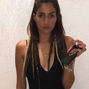 תמונה של בחורה עם חולצה שחורה מביטה אל המצלמה, על השיער ראסטות בקטנה מאחורה